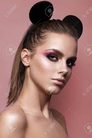 beautiful with professional makeup and mickey mouse ears on pink background trendy colorful smoky