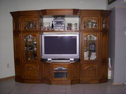 curved dark brown wooden wall unit entertainment center with glass doors and racks on the floor