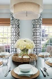 dining table lined with beige tufted dining chairs illuminated by a beige tiered drum pendant restoration hardware two tier linen shade pendant