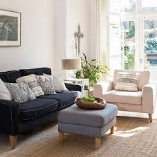 white living room with charcoal sofa and foot stall
