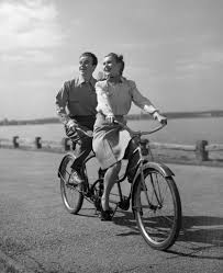 1950s happy couple man woman riding tandem bike bicycle built for