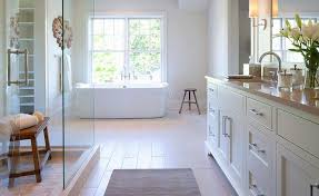 fantastic bathroom boasts a seamless glass walk in shower filled with a freestanding bench facing a cream washstand topped with taupe quartz fitted with his