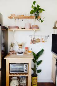 An IKEA cart and shelving in the kitchen hold Cai and Britt's ceramic  dishes and mugs