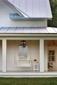 modern farmhouse exterior porch swing white siding with metal roof black lantern lighting