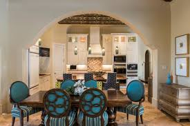 moroccan dining room with bright turquoise chairs and sy wood table