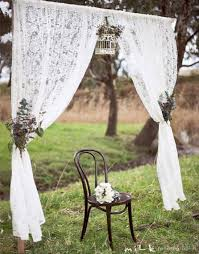 a classic looking wedding photo booth set up outdoors with lace curtains and a simple wooden