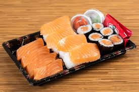 an excellent bination of four pieces of salmon sashimi four pieces of salmon nigiri sushi and salmon maki cut in six pieces ginger wasabi and