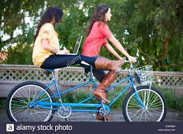 two women riding a tandem bike while the woman on back surfs the