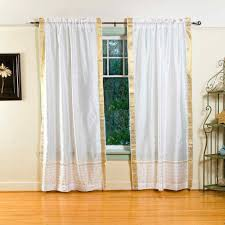 interior white curtains on black hook and brown wooden laminate floor connected by cream wall