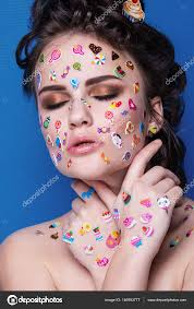 beautiful fashion with luxury professional makeup and funny emoji stickers glued on the face young woman with cupcake in hands photo by