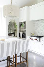 stunning kitchen features an oly studio meri drum chandelier illuminating a kitchen island lined with white and gray striped counter stools