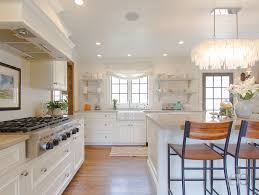 chic cottage kitchen features a west elm large rectangle hanging capiz chandelier hanging over a white center island topped with cream natural stone lined