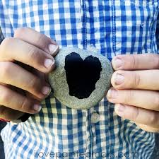 boy holding a painted rock with a black heart on it how to seal painted