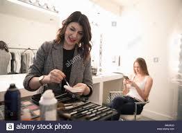 female makeup artist preparing makeup for model preparing for photo shoot
