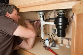 plumber using adjule pliers on sink drain