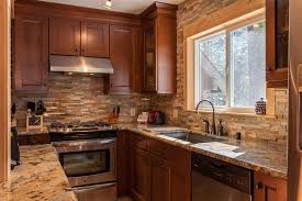 small craftsman galley kitchen with stacked stone backsplash brown cabinets and beige granite countertops