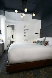 bedroom wall lighting ideas. dark ceiling white walls bed with pop of color quote as wall art bedroom lighting ideas