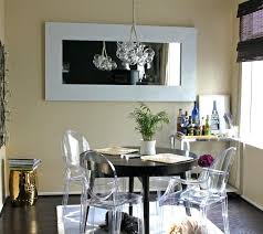 glass dining room light fixture above black round table with modern chairs for small spaces and