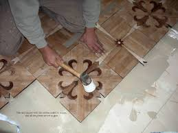 starting parquet installation tapping parquet tiles to insure adhesion