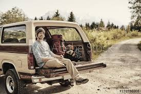 Young man sitting on back of pickup truck, looking at camera ...