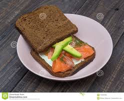 Sandwich With Salmon Avocado And Black Bread On A Plate Stock Image