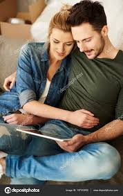 beautiful loving couple using tablet in new house photo by