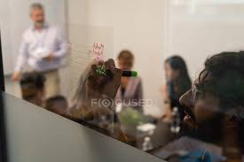 male executive writing on glass wall in office young woman conference room stock photo 222562660