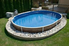 oval pool filled with water resting on a bed of white stones in a