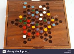 Wooden Board Game With Pegs Chinese checkers colour pegs on a wooden board A game of strategy 98