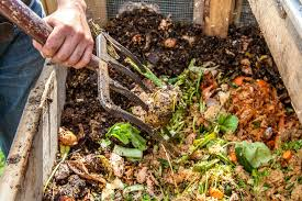 Close Up Of A Gardener Turning Compost Pile With Garden Fork