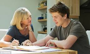 Parents Helping Children With Homework In Kitchen   Visions In