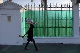 photo essay  haiti    s earthquake victims wonder where the    a w  walks past the fence that covers the view of what was the presidential palace