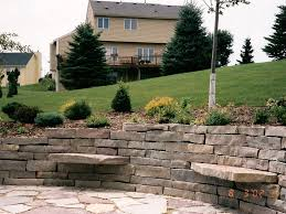 large stone retaining wall landscape with sitting stones and patio