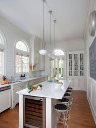 Elegant medium tone wood floor enclosed kitchen photo in New Orleans with  shaker cabinets, white