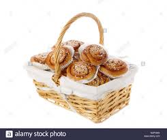 wicker basket filled with cinnamon rolls in tins of greaseproof paper isolated on white