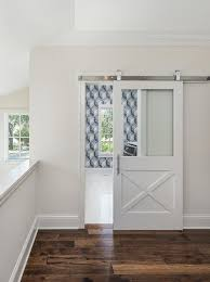 white and blue laundry room with glass and wood barn door on rails