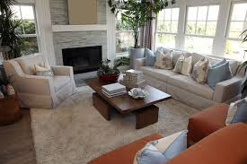 designing a living room space. living room space with two reddish brown chairs, one beige sofa and armchair designing a
