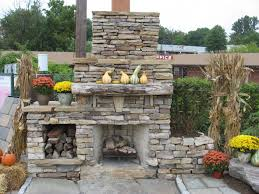 fresh flowers on simple pots and amusing outdoor stone fireplace beside small logpond