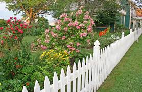 a long white picket fence with beautiful landscaping along the length of it the