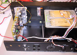 quad amplifier information and modification ~ the quad 405 the old power supply capacitors and output connectors removed ready for some direct rewiring looking at the holes in the chassis for