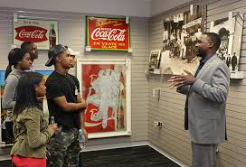 career exploration at coca cola a photo essay   cehd students look at photos of coca colas history as jamal booker explains them