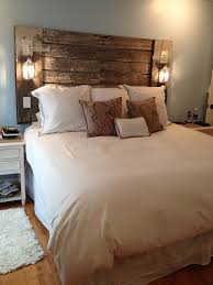 The headboard my husband made me out of reclaimed barn lumber and candle  lanterns. Love it! Love the outlet in the headboard