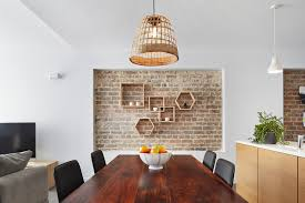 geometric timber wall shelves combined with exposed bricks are definitely a focal point of this loft