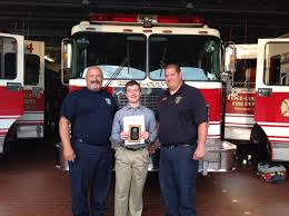 fire prevention essay contest bishop kearney school of rochester  bryce clark holding his award standing next to firefighter ralph rizzo left