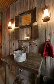 a galvanized pail is brought to life as a sink in this rustic barn board bathroom