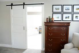 white stained wood sliding barn door hanging on black rod next to rustic brown chinese cabinet and armchair on grey flooring