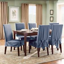 blue fabric upholstered dining chair covers and rectangular dining table on traditional pattern rug match with beige curtain and light green wall paint