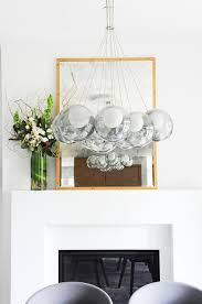 brass rivet mirror on sleek white fireplace mantel