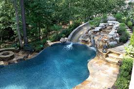 this beautiful swimming pool has its own natural rock waterfall that gives it a special and rustic charm landscape around it is really beautiful
