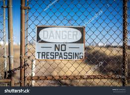 danger no trespassing sign with chain link fence rust and empty field